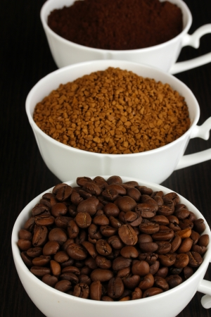 Different types of coffee in three cups on wooden table photo