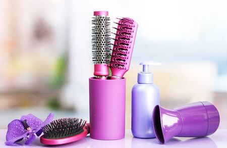 Hair brushes, hairdryer and cosmetic bottle in beauty salon  photo