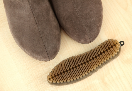Brush for suede shoes, on wooden background photo