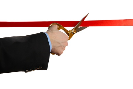 Man's hand cutting red ribbon with pair of scissors isolated on white Stock Photo - 18325783