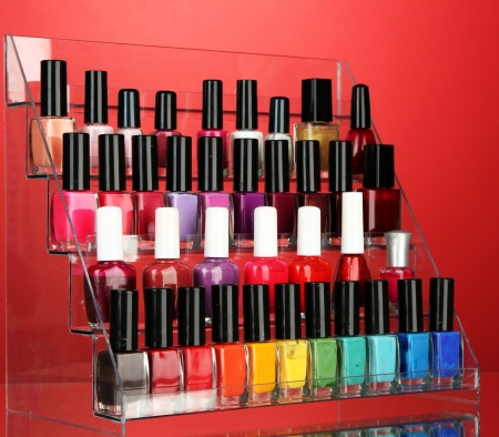 Bright nail polishes on shelf on red background photo