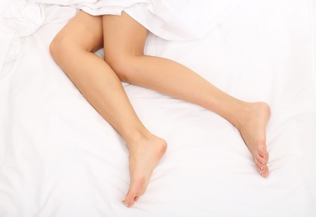 Young woman lies on her bed with long legs photo