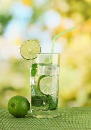 Glass of water with ice, mint and lime on table on bright background Stock Photo
