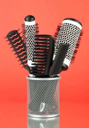 Iron basket with combs and round hair brushes, on color background photo