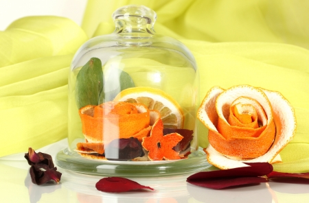 Decorative rose from dry orange peel in glass vase on green fabric background photo
