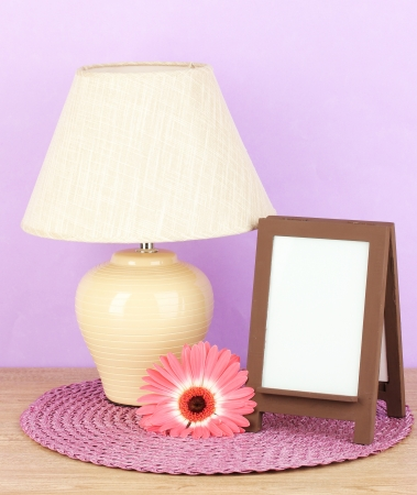 Brown photo frame and lamp on wooden table on lilac wall background Stock Photo - 18447945