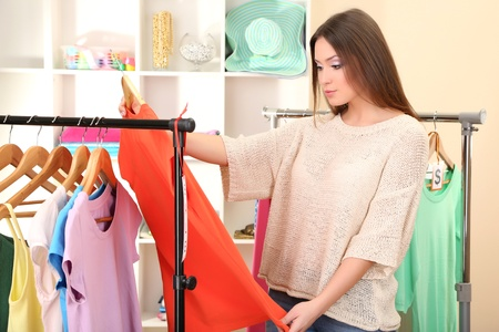 clothing store: Young girl in shop buying clothes Stock Photo