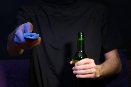 Man hand holding a TV remote control and beer bottle, on dark background photo