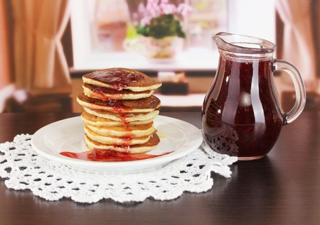 Sweet pancakes on plate with jam on table in room Stock Photo - 18474175