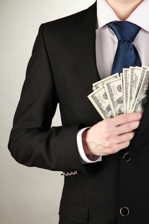 Business man hiding money in pocket on grey background Stock Photo - 18474095