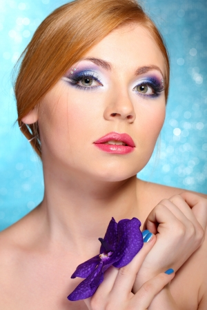 Beautiful young woman with glamour make up and flower on blue background photo