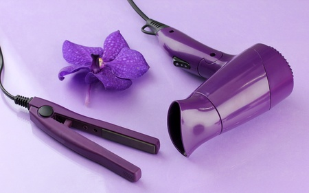 Hair dryer and straighteners  on purple background photo