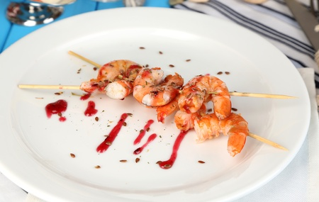 Grilled shrimp with sauce on plate on wooden table close-up photo