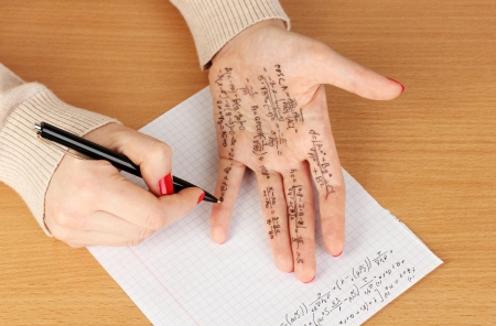 Write cheat sheet on hand on wooden table close-up Stock Photo - 18474300
