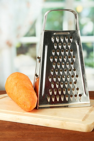 Metal grater and carrot on cutting board, on bright background photo