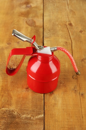 Red oil can, on wooden background Stock Photo - 18474262