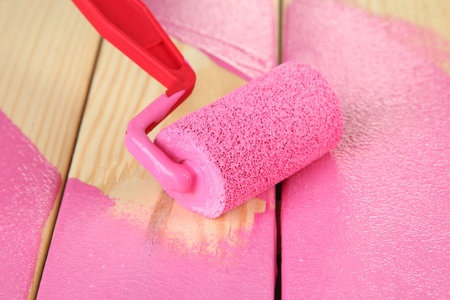 modernise: Paint roller brush with pink paint, on wooden background