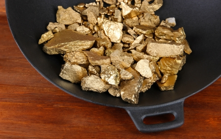 tough luck: Gold pan with golden nuggets inside on wooden background