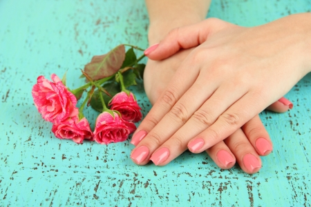 Woman hands with pink manicure and flowers, on color background Stock Photo - 18474253