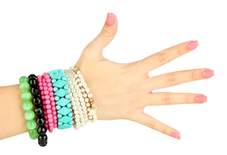 hand wear: Female hand with pink manicure and bright bracelets, isolated on white Stock Photo
