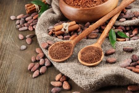 cacao: Cacao en polvo y cacao en grano en el fondo de madera Foto de archivo
