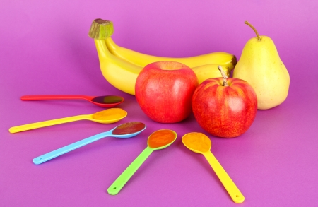 Baby puree in spoons with fruits on purple background photo
