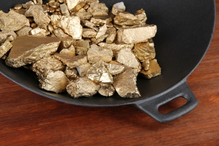Gold pan with golden nuggets inside on wooden background Stock Photo - 18475211