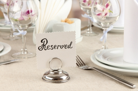 wedding table: Reserved sign on restaurant table with empty dishes and glasses