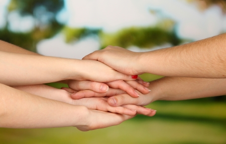 grasp: Many hands on nature background Stock Photo