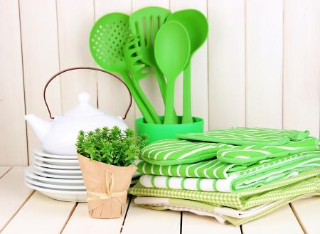 Paramètres de cuisine: ustensiles, maniques, les serviettes et le reste sur la table en bois