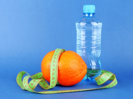 Orange with measuring tape, bottle of water, on color background Stock Photo - 18475035