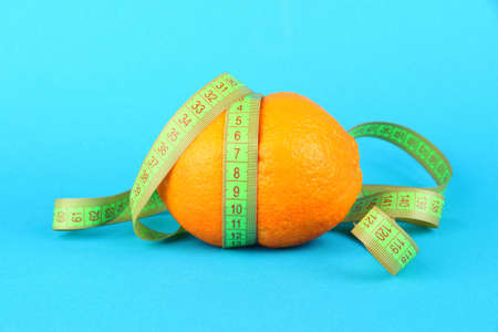 Orange with measuring tape, on color background Stock Photo - 18475214