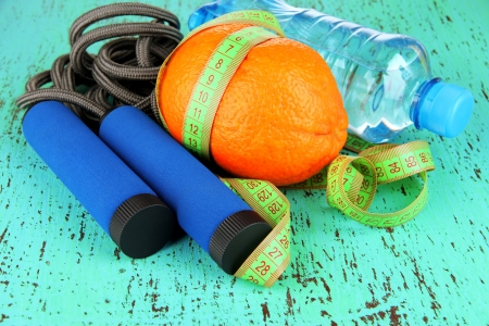 Orange with measuring tape,skipping rope and bottle of water, on color wooden background Stock Photo - 18475204