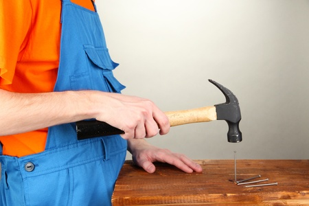 Builder hammering nails into board on grey background