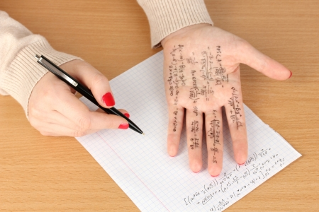 cheat: Write cheat sheet on hand on wooden table close-up