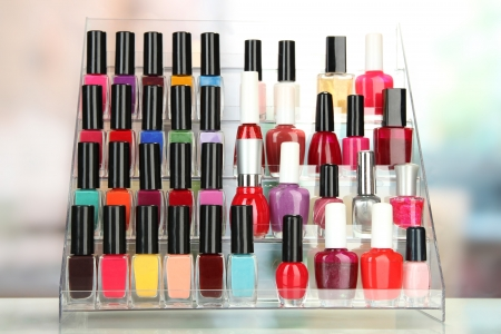 Bright nail polishes on shelf in beauty salon photo