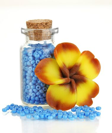Little bottle full with colorful beads isolated on white photo