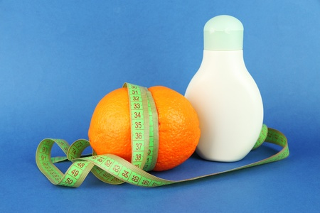 Orange with measuring tape and body cream, on color background Stock Photo - 18490994