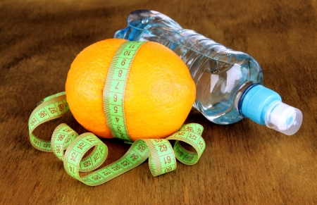 Orange with measuring tape, bottle of water, on wooden background Stock Photo - 18491094
