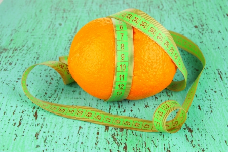 Orange with measuring tape, on color wooden background Stock Photo - 18491098