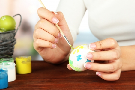 Young woman painting Easter eggs, on bright background Stock Photo - 18508493