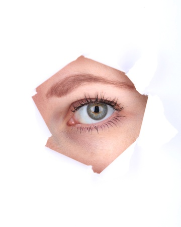 Female eye looking through hole in sheet of paper photo