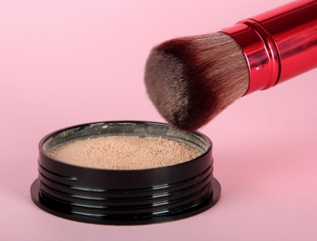 Powder and brush in hand on pink background Stock Photo