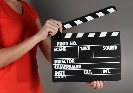 Movie production clapper board in hands on grey background Stock Photo - 18508446
