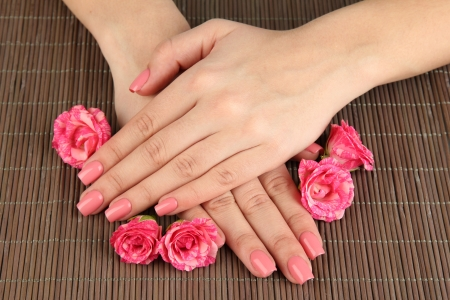 manicure nails: Woman hands with pink manicure and flowers, on bamboo mat background