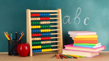 Toy abacus, books and pencils on table, on school desk background photo