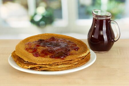 rubicund: Sweet pancakes on plate with jam on table in kitchen
