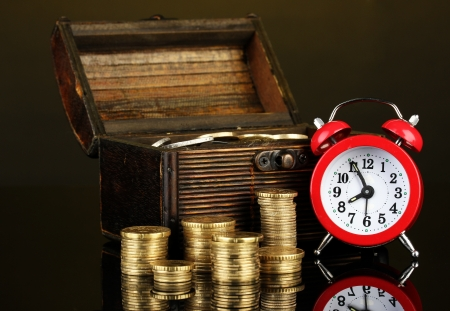 Alarm clock with coins in chest on dark background photo