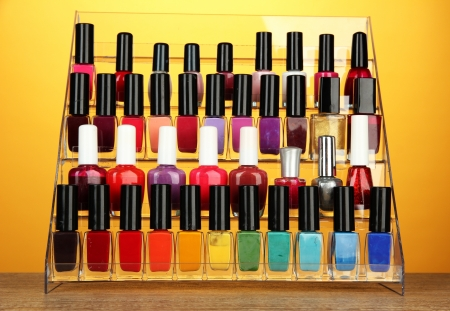 Bright nail polishes on shelf on yellow background photo