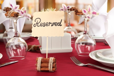 Reserved sign on restaurant table with empty dishes and glasses photo